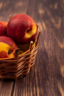 Вид сверху здоровых и свежих персиков на ведре на деревянной стене