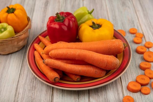Вид сверху здорового болгарского перца на тарелке с морковью с желтым болгарским перцем на ведре с нарезанной морковью, изолированной на сером деревянном фоне