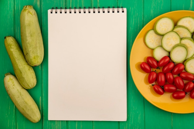 コピースペースのある緑の木製の壁に分離されたズッキーニとプラムトマトと黄色のプレート上の健康なみじん切りズッキーニスライスの上面図