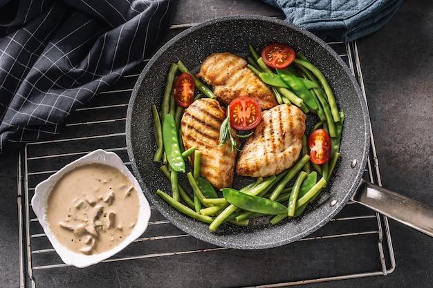 Вид сверху здоровой приготовленной курицы и овощей на сковороде со сливочно-грибным соусом сбоку, помещенной на черном фоне с полотенцем и прихваткой.