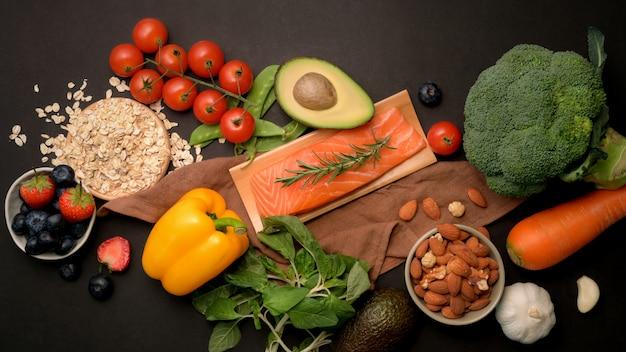 Вид сверху ассортимента здоровой пищи с лососем, фруктами, овощами и семенами на черном столе