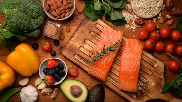 Вид сверху ассортимента здоровой пищи с лососем, фруктами, овощами и семенами на деревенском столе