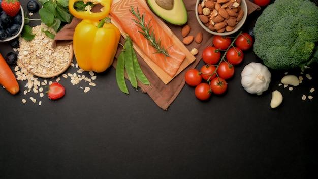 Вид сверху ассортимента здоровой пищи чистый выбор еды с лососем, фруктами, овощами, семенами и копией пространства на черном столе