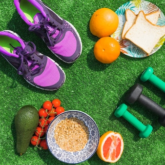 Top view of healthy food with dumbbells and pair of shoes on green turf