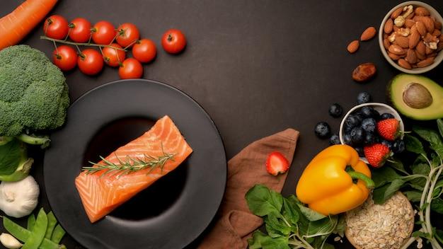 Вид сверху здоровой пищи с лососем, фруктами, овощами, семенами и копией пространства на темном столе