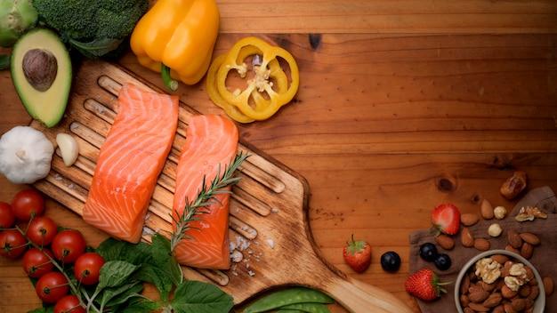 Вид сверху здоровой пищи с лососем, фруктами, овощами, семенами и копией пространства на деревенском столе