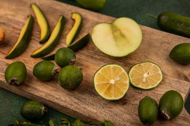 Feijoas 아보카도 슬라이스 반 라임과 녹색 배경에 나무 주방 보드에 고립 된 사과와 같은 건강 식품의 상위 뷰