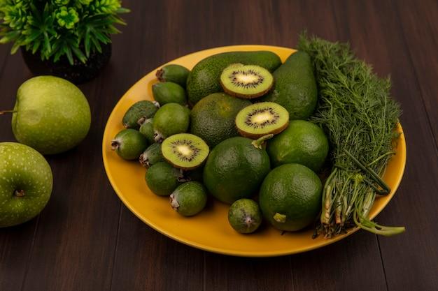 Вид сверху здоровых фруктов, таких как авокадо, киви, фейхоас и лайм на желтой тарелке на клетчатой ткани на деревянной стене