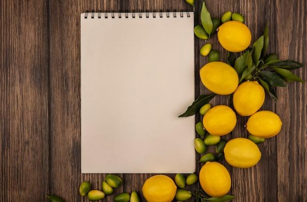 복사 공간이 나무 표면에 고립 된 레몬과 kinkans와 같은 건강한 과일의 상위 뷰