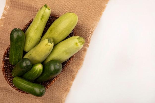 Вид сверху на здоровые зеленые овощи, такие как огурцы, цуккини, на ведре на мешковине на белом фоне с копией пространства