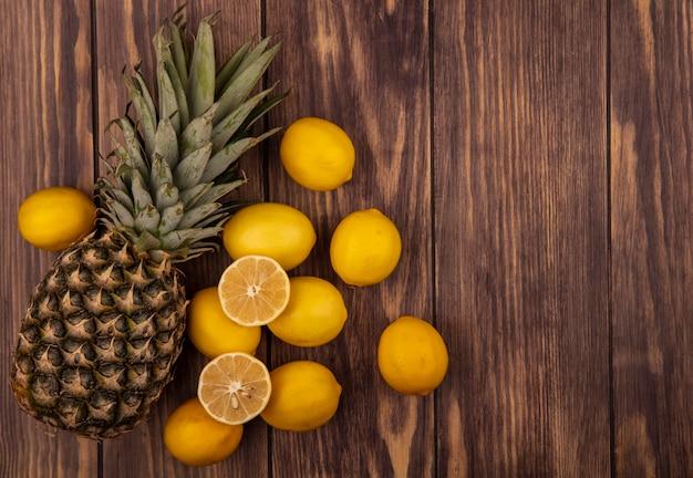 コピースペースのある木製の表面に分離されたパイナップルと健康的な半分と全体のレモンの上面図