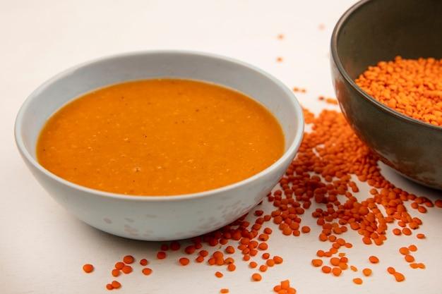 白い表面に分離された新鮮なレンズ豆とボウルの健康なレンズ豆のスープの上面図