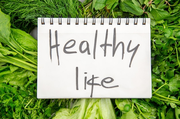 白いテーブルの上の新鮮な緑の束のスパイラルノートの健康的な生活の碑文の上面図
