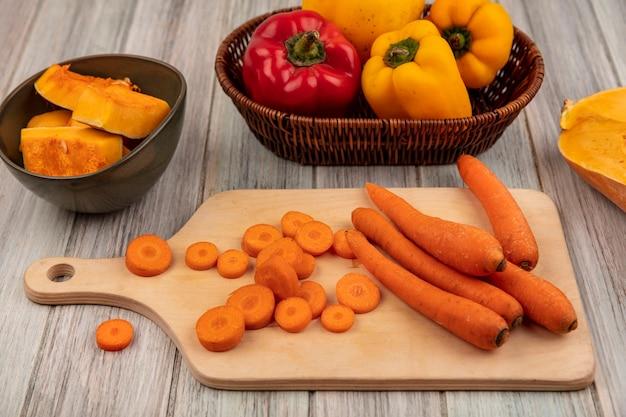 Вид сверху здоровой оранжевой моркови на деревянной кухонной доске с разноцветным болгарским перцем на ведре с ломтиками тыквы на миске на серой деревянной поверхности