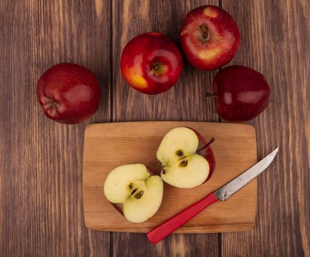 木製の壁に分離されたリンゴとナイフで木製のキッチンボード上の健康な赤いリンゴの上面図