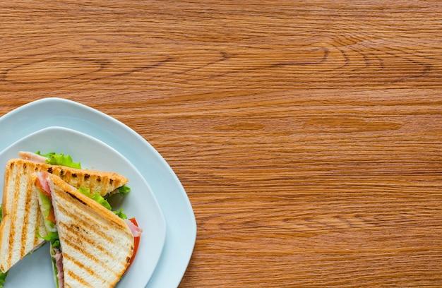 木製の背景上の健康的なサンドイッチトーストのトップビュー