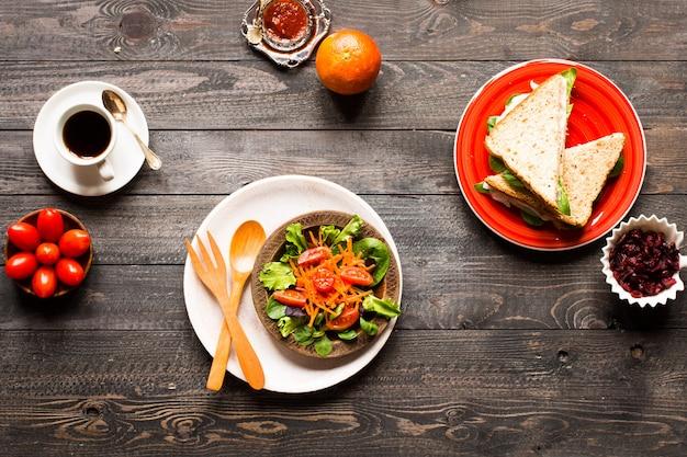 木製の背景に、レタスとヘルシーなサンドイッチトーストのトップビュー