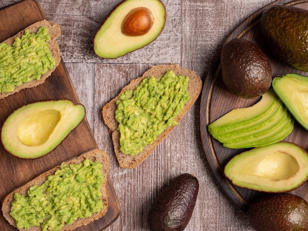 Вид сверху здоровых бутербродов с авокадо на деревянной доске