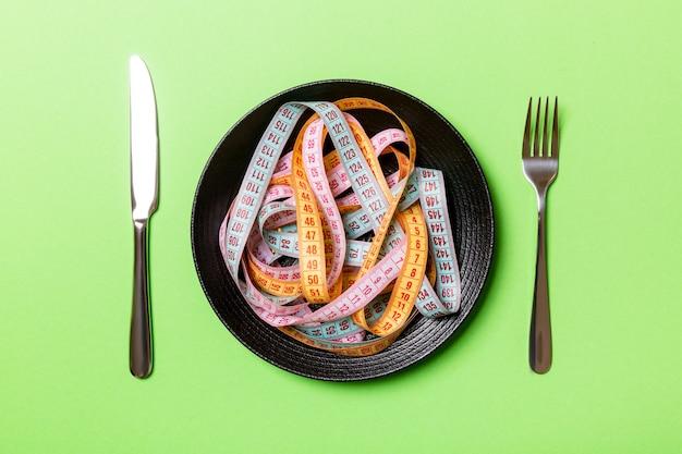 Вид сверху кучи красочных измерительных лент в пластине на зеленом фоне. концепция диеты с копией пространства.