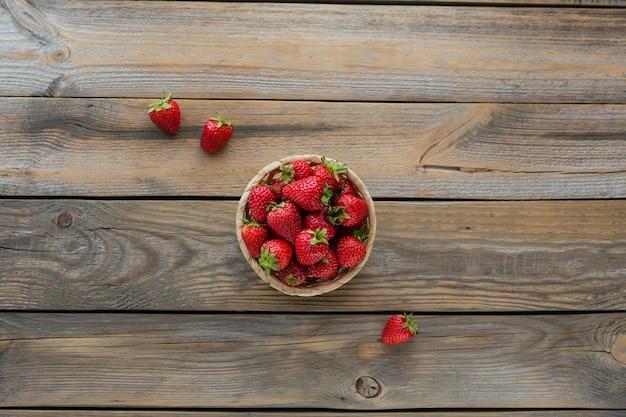 素朴な木製の背景のバスケットに新鮮なイチゴのヒープの上面図。健康的な食事とダイエット食品の概念。