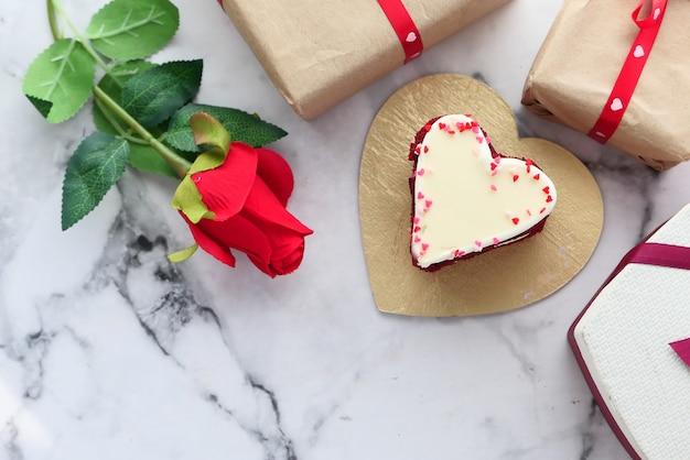 白い背景の上のハート形のケーキ、ギフトボックス、バラの花の上面図