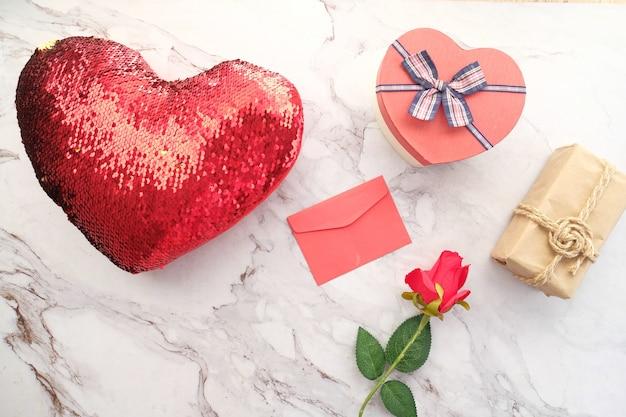 ハート形のギフトボックス、花、タイルの背景に封筒の上面図
