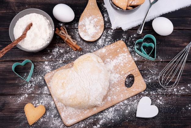 Вид сверху теста в форме сердца с кухонной утварью