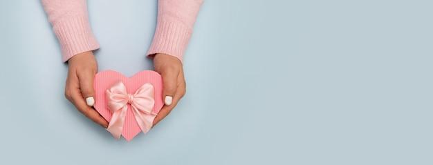 복사 공간 배너와 컬러 표면에 여성 손에 심장 모양의 선물 상자의 상위 뷰