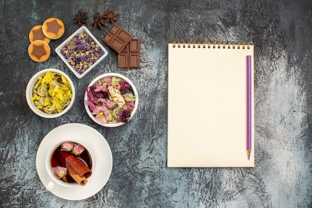 Вид сверху на травяной чай с сухими цветами и блокнот с ручкой на серой земле