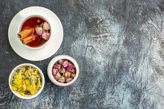 Вид сверху травяного чая с сухими цветами на сером фоне
