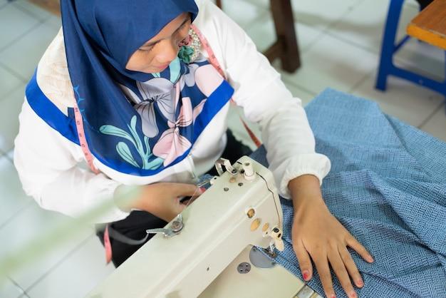 ヒジャーブの女性が縫製生地を仕立てる上面図