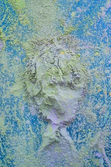 Top view of holi festive powder background on blue background