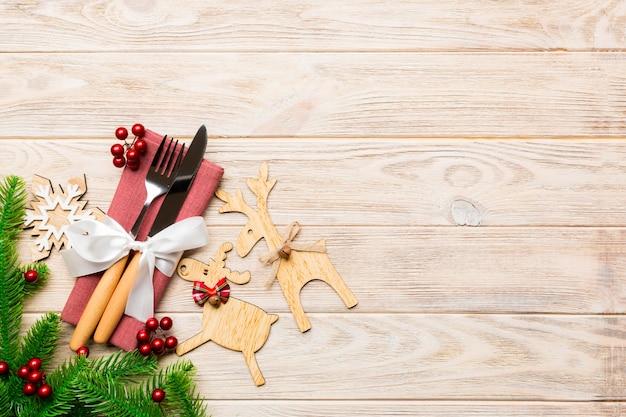 Вид сверху праздничных объектов на деревянных фоне. посуда перевязана лентой на салфетке. рождественские украшения и олени с копией пространства. концепция новогоднего ужина.