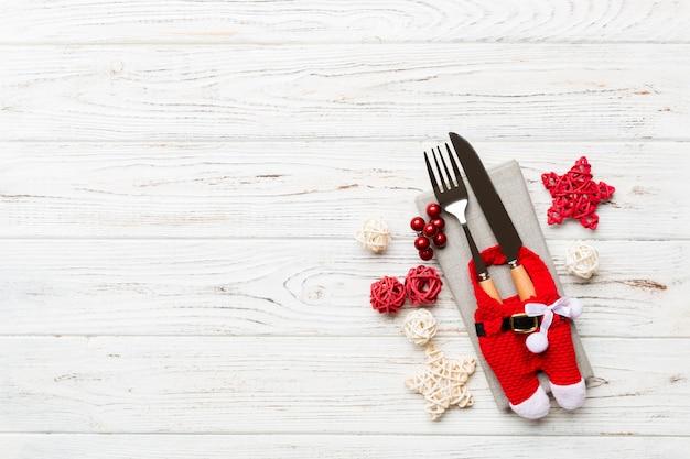 Вид сверху праздничного набора вилки и ножа на деревянных фоне. рождественские украшения и игрушки с копией пространства. новогодняя концепция.