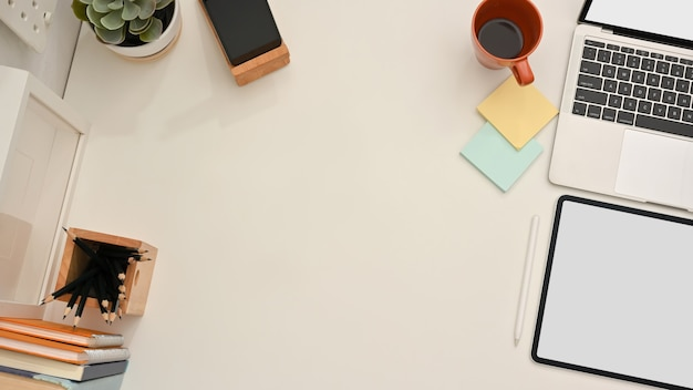タブレット、ラップトップ、文房具、テーブル上のコピースペース、クリッピングパスを備えたホームオフィスデスクの上面図