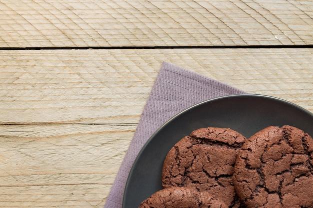 木製の背景の黒い皿に自家製チョコレートクッキーの平面図です。ホームベーカリー