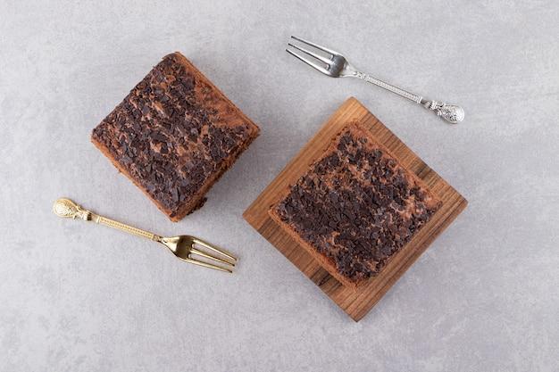 포크가 달린 나무 판자에 있는 홈메이드 초콜릿 케이크의 최고 전망.