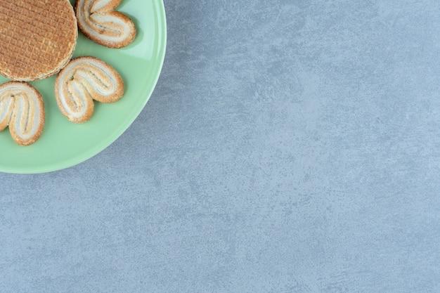 사진의 녹색 접시 모서리에 수 제 쿠키의 상위 뷰.