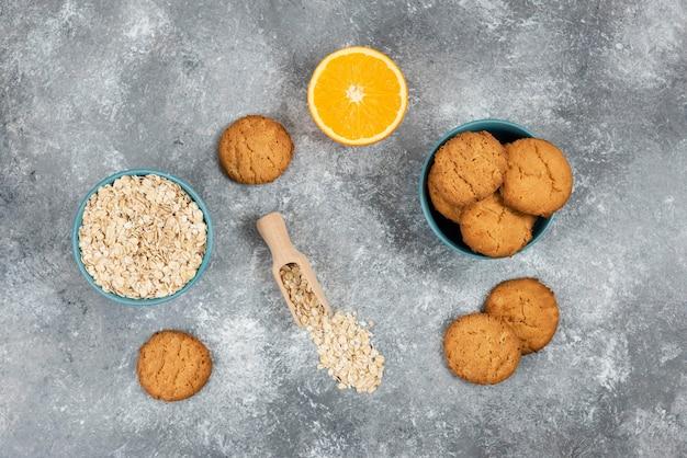 나무 판자에 있는 홈메이드 쿠키와 오렌지가 든 오트밀의 최고 전망.