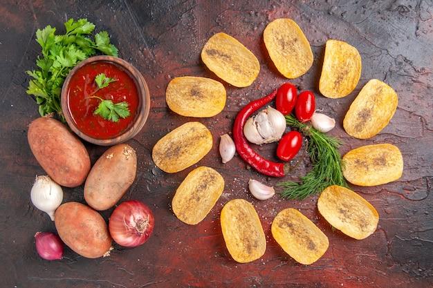 自家製のおいしいクリスピーチップス赤唐辛子ニンニクグリーントマトケチャップポテトタマネギの暗いテーブルの上面図