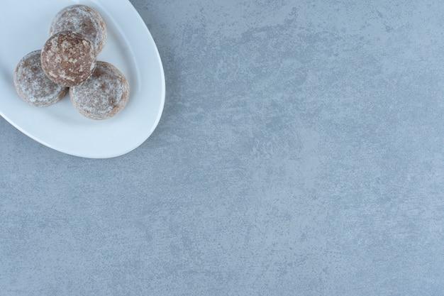 白いプレート上の自家製の新鮮なクッキーの上面図。