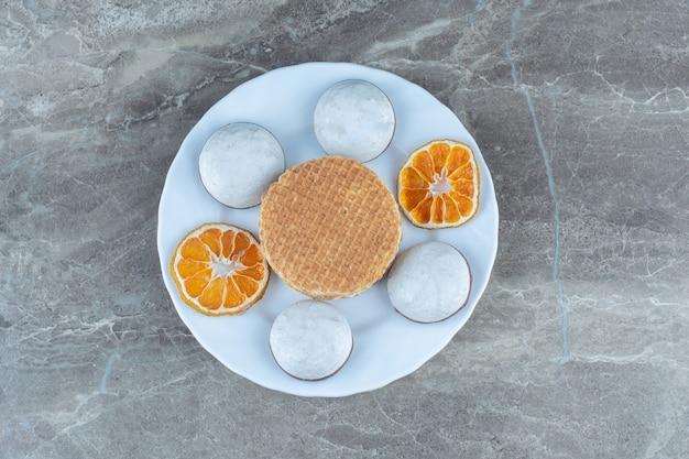 ワッフルとドライオレンジスライスを添えた自家製の新鮮なクッキーの上面図。