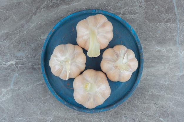 Вид сверху самодельного рассола чеснока на синей деревянной тарелке.