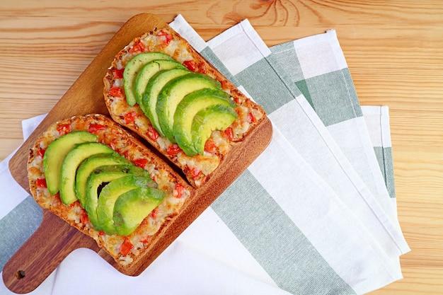 木製ブレッドボードにトマトとスライスしたアボカドを添えた自家製グリルチーズトーストの上面図
