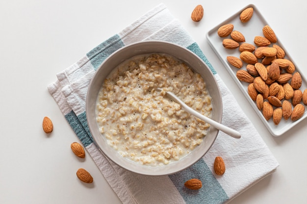 ボウルにナッツアーモンド、白い背景の上のセラミックスプーンと自家製オートミールのお粥の上面図。健康朝食食品の概念。スペースをコピーします。