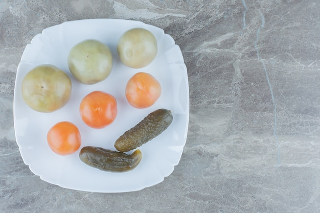 自家製漬物の上面図。白い皿に未熟なトマトとキュウリ。