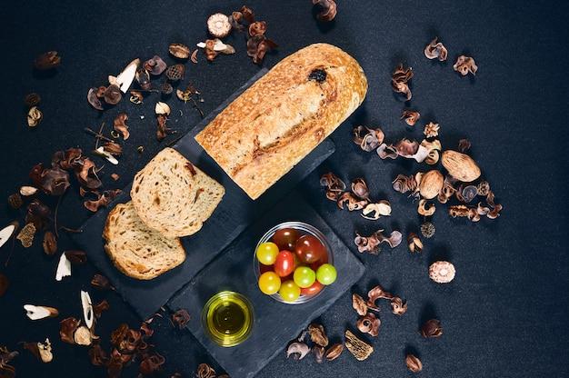 Вид сверху домашнего томатного хлеба с парой ломтиков, нарезанных в сланце, с оливковым маслом и миской с помидорами черри