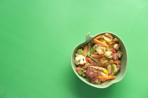 緑の机の上のボウルに自家製野菜サラダの上面図