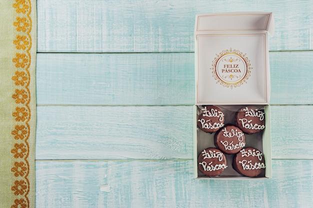 Вид сверху шоколадного медового печенья в коробке с надписью happy easter - paes de mel
