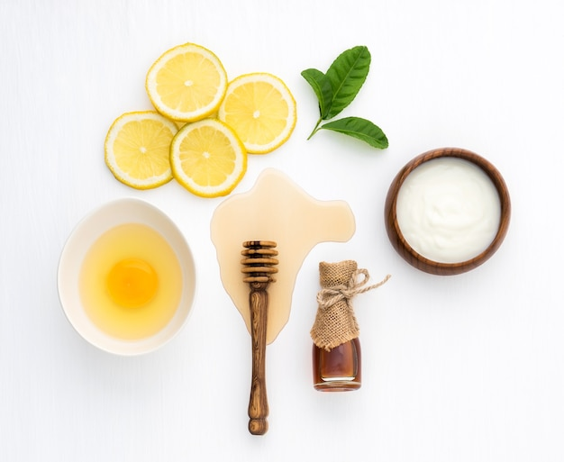 木製の白い背景の上の蜂蜜ヨーグルトとレモンの上面図